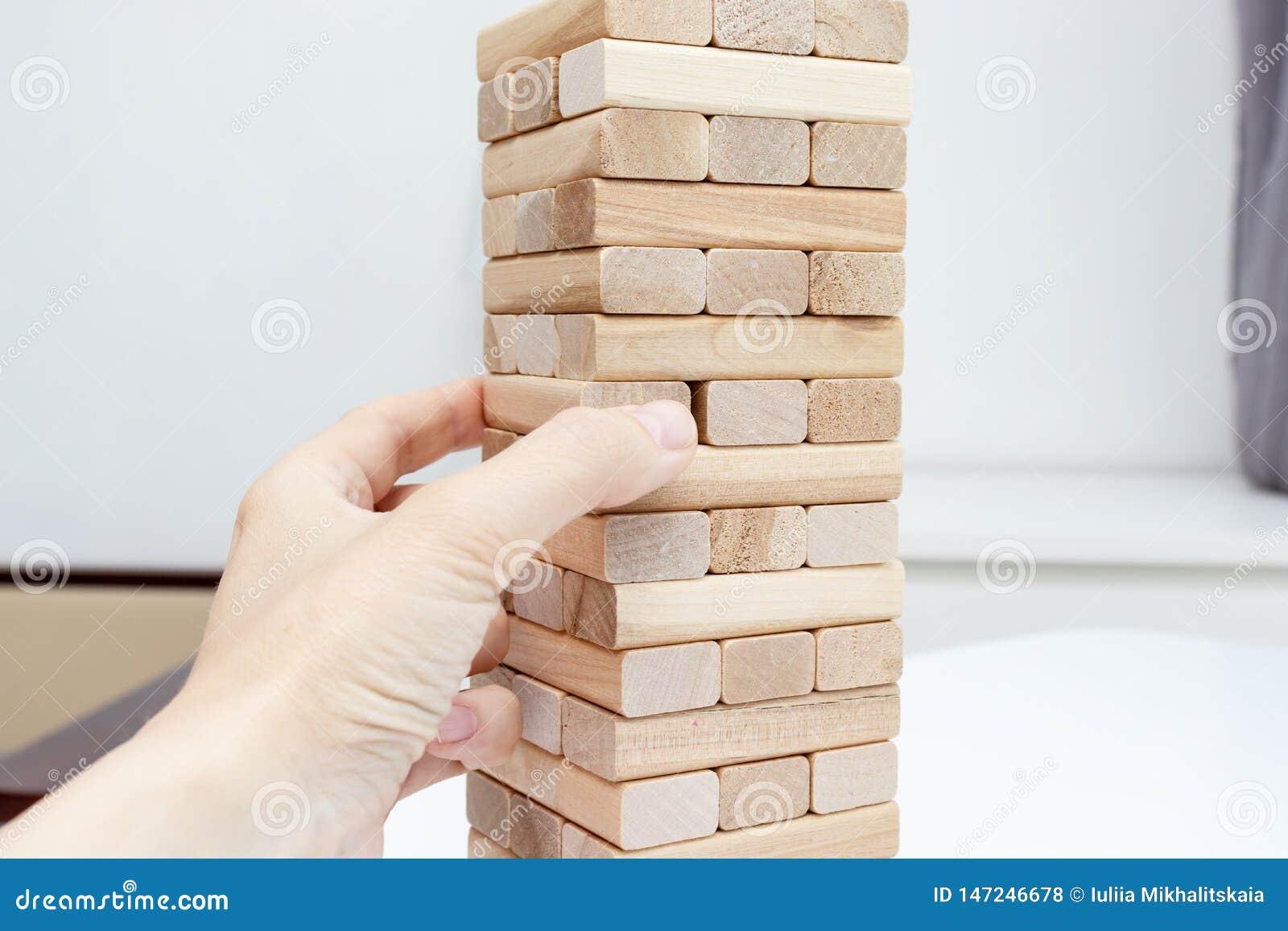 Ein jugendlicher kaukasischer Junge, der Holzklotzturm-Brettspiel f?r das ?ben seiner k?rperlichen und Geistesf?higkeit und Unter