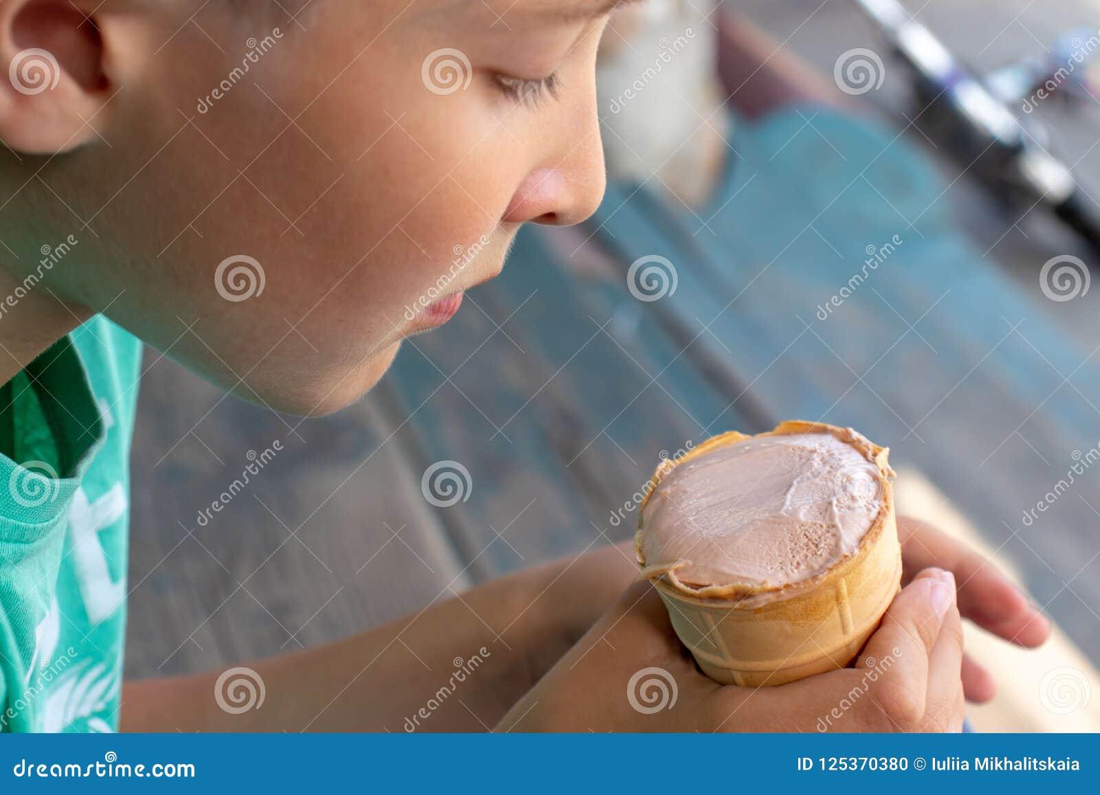 Ein Junge, der auf hölzerner Treppe sitzt und Eiscreme isst
