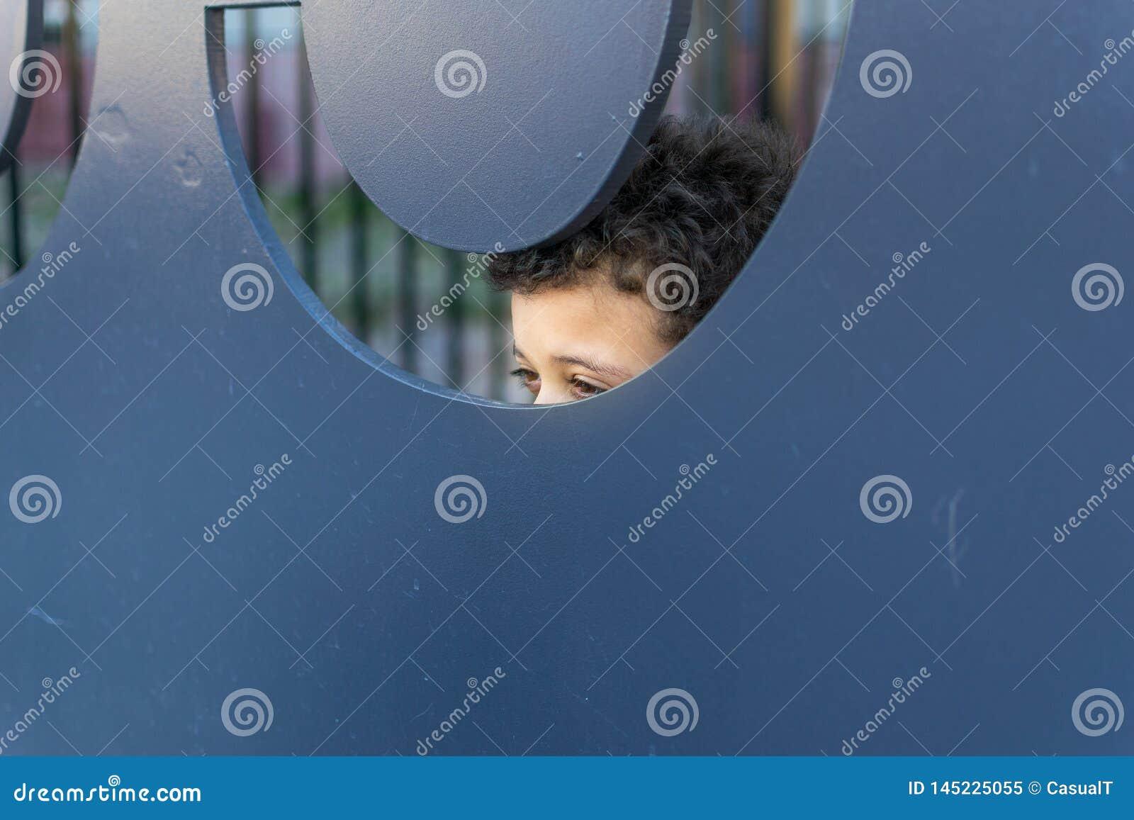 Ein Junge, der playfully heraus von hinten einen großen Metallausschnitt späht