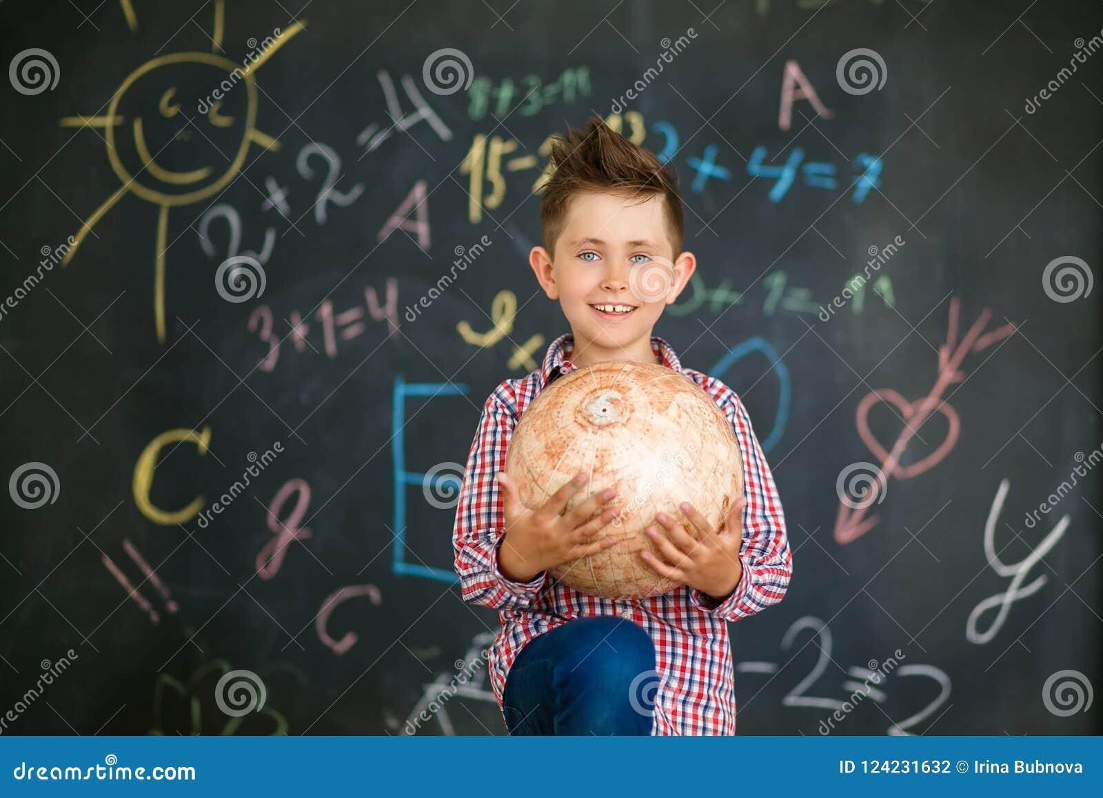 Ein Junge hält eine Kugel vor einer Schulbehörde