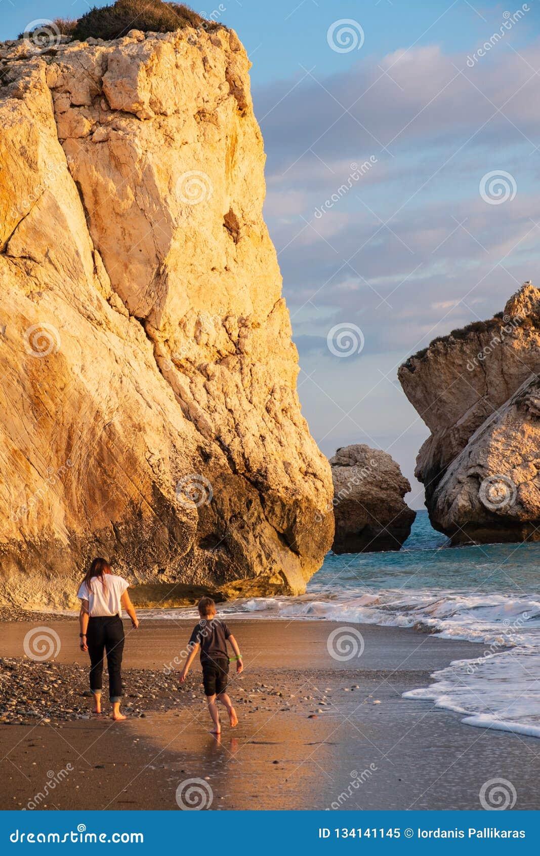 Ein Junge und ein Mädchenspaziergang barfuß am Strand againt die PETRA-tou Romiou-Geburtsortfelsen der Aphrodite gebadet im Nachm