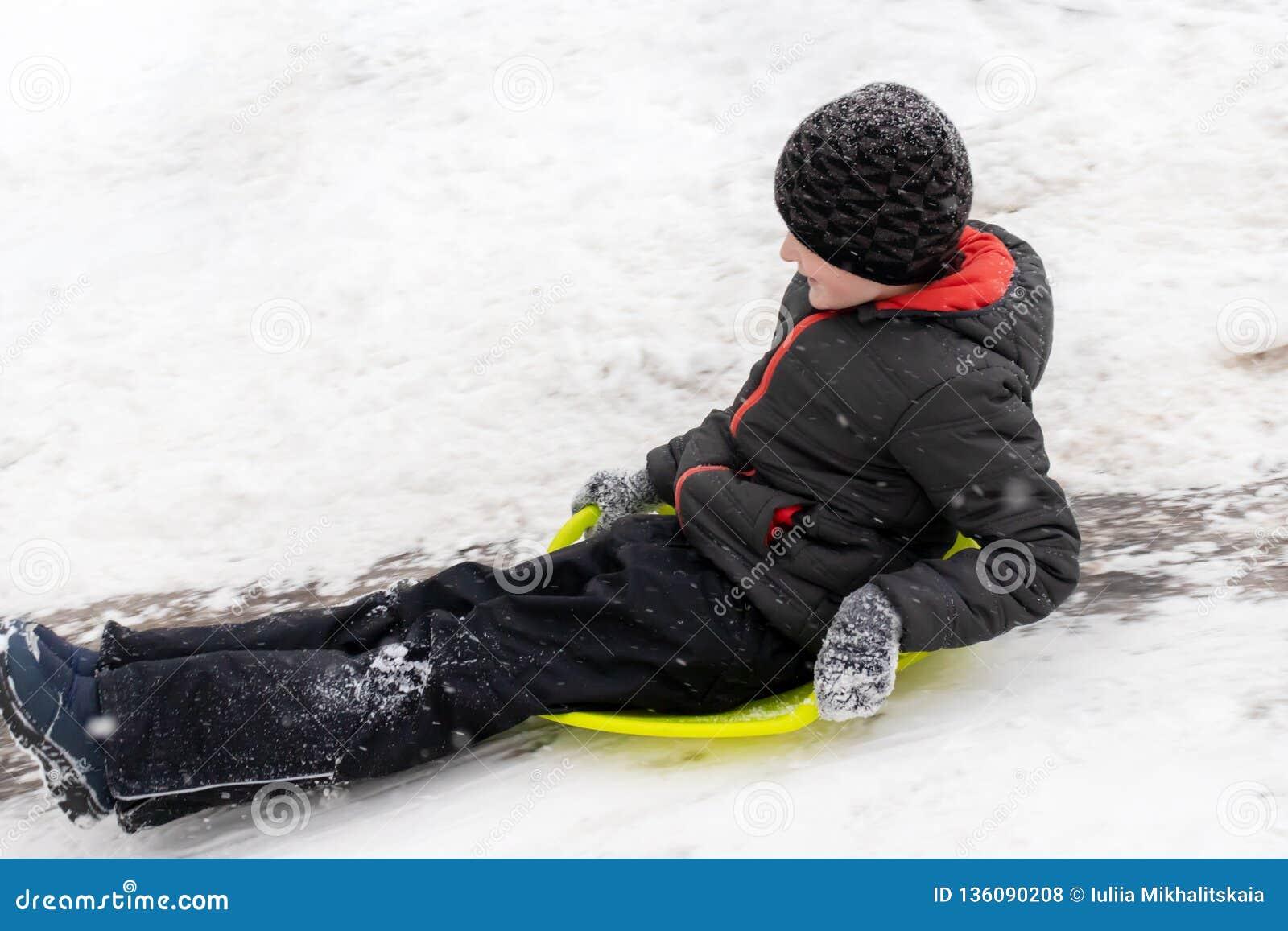 Ein Junge von sieben Jahren alt reitet das Dia, hinunter den Hügel auf grünen Eisschlitten Konzept von Winterbetrieben, von Erhol