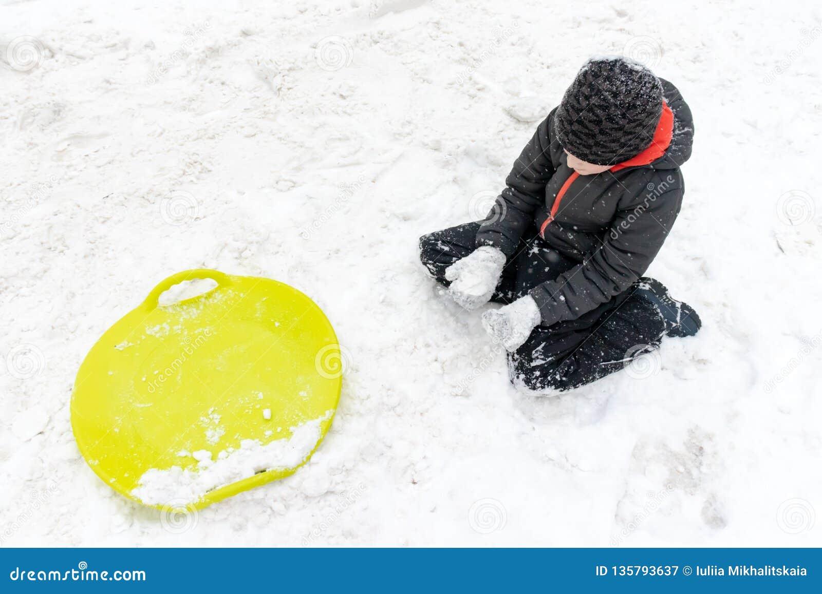 Ein Junge von sieben Jahren alten Sitzen auf dem Schnee und ein grüner Plastikuntertassenschlitten, der nahe ihm liegt Konzept vo