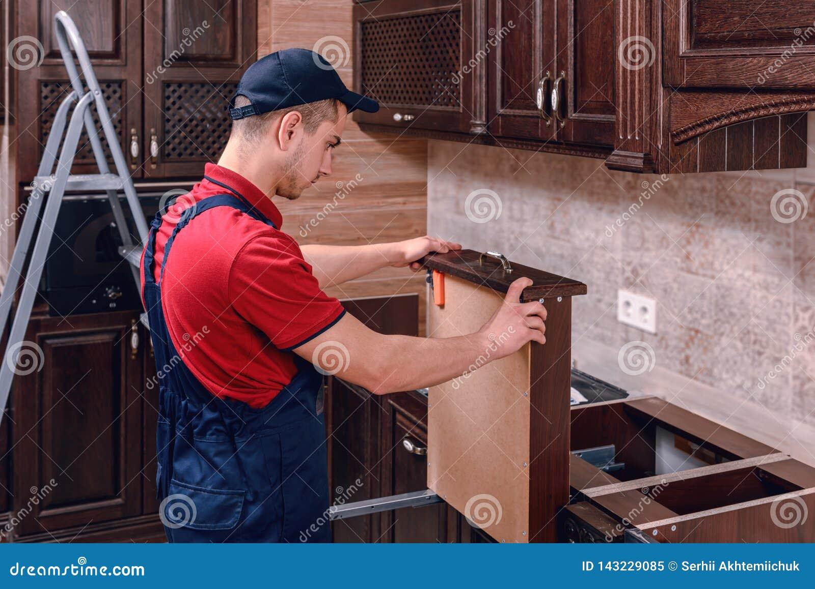 Ein junger Arbeitnehmer installiert ein Fach Installation von modernen hölzernen Küchenmöbeln