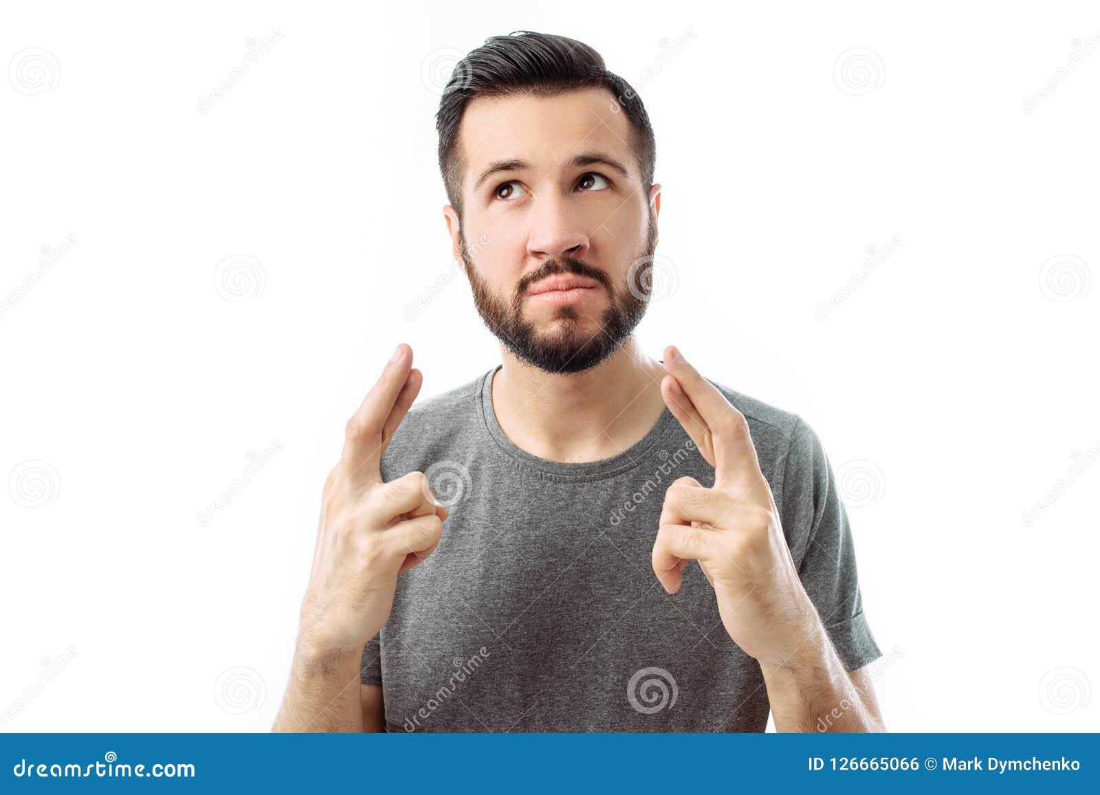 Ein junger bärtiger Mann, mit großer Hoffnung, kreuzt seine Finger als er
