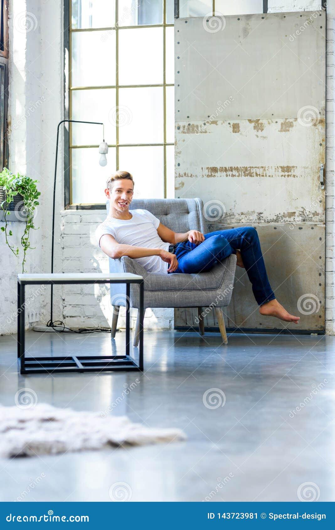 Ein junger gutaussehender Mann, der in einem Lehnsessel in einem Dachbodenart-APAR sich entspannt