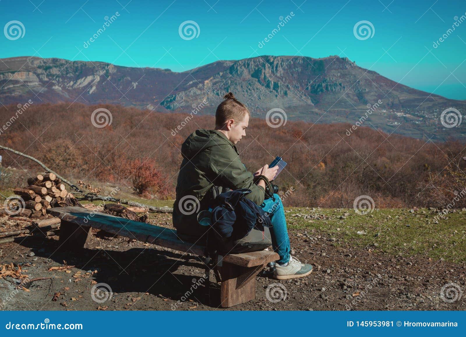 Ein junger Kerl, der für das Wandern gekleidet wird, sitzt hoch in den Bergen und schaut einen Handy