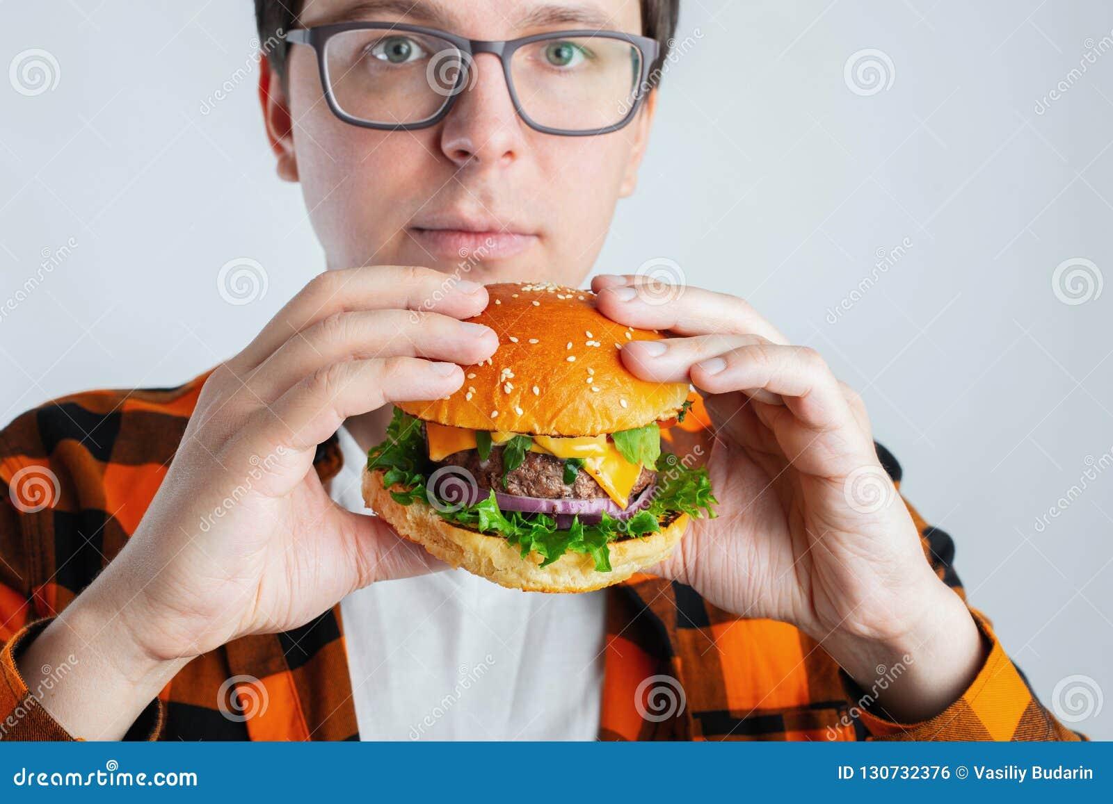 Ein junger Kerl mit den Gläsern, die einen frischen Burger halten Ein sehr hungriger Student isst Schnellimbiß Heiße hilfreiche N