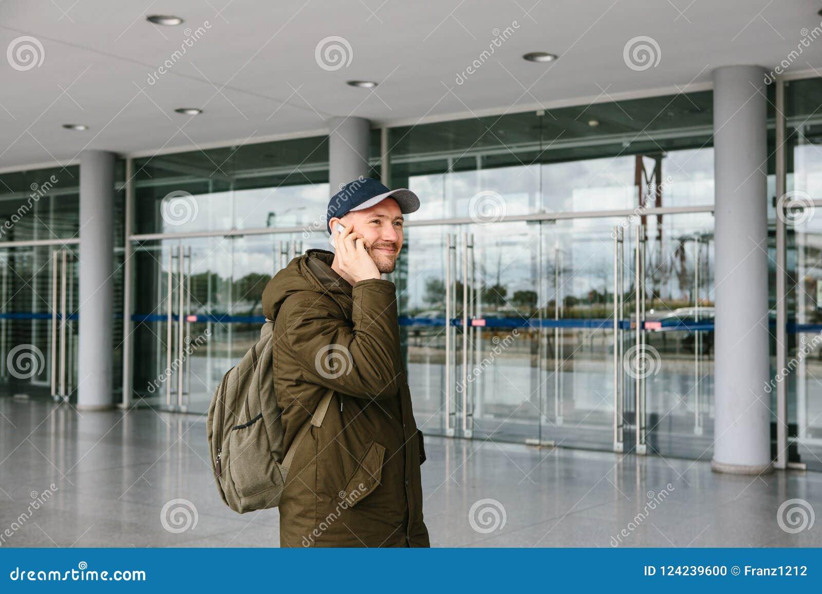 Ein junger männlicher Tourist am Flughafen oder nahe einem Einkaufszentrum oder einer Station ruft ein Taxi oder spricht an einem