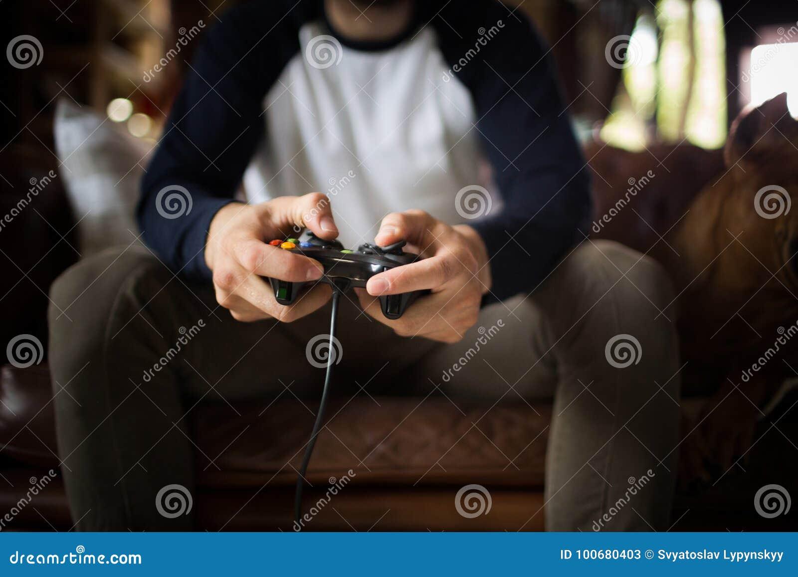 Ein junger Mann, der den Steuerknüppel, Videospiel spielend hält