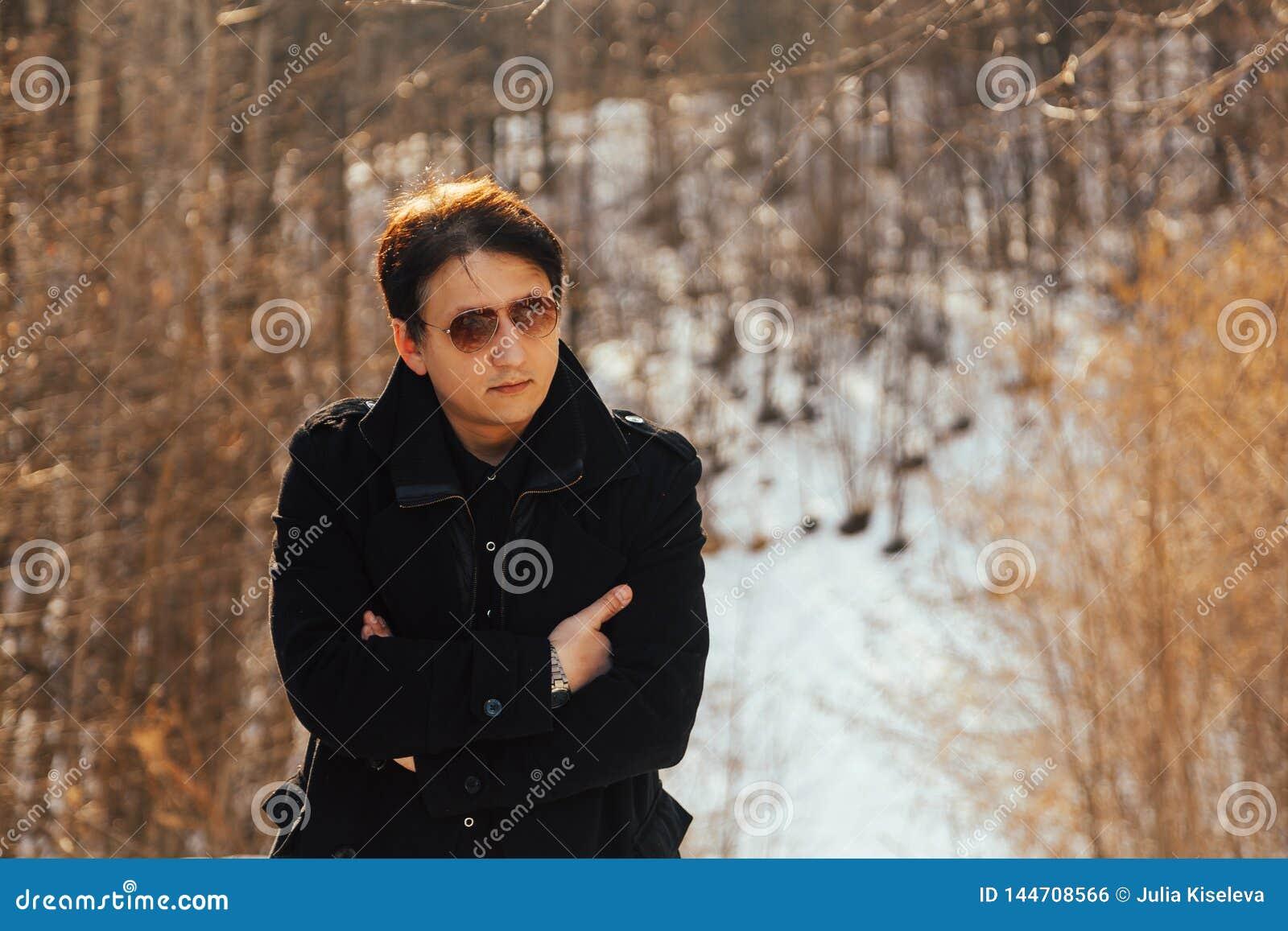Ein junger Mann in einem Mantel und in der Sonnenbrille in der Natur