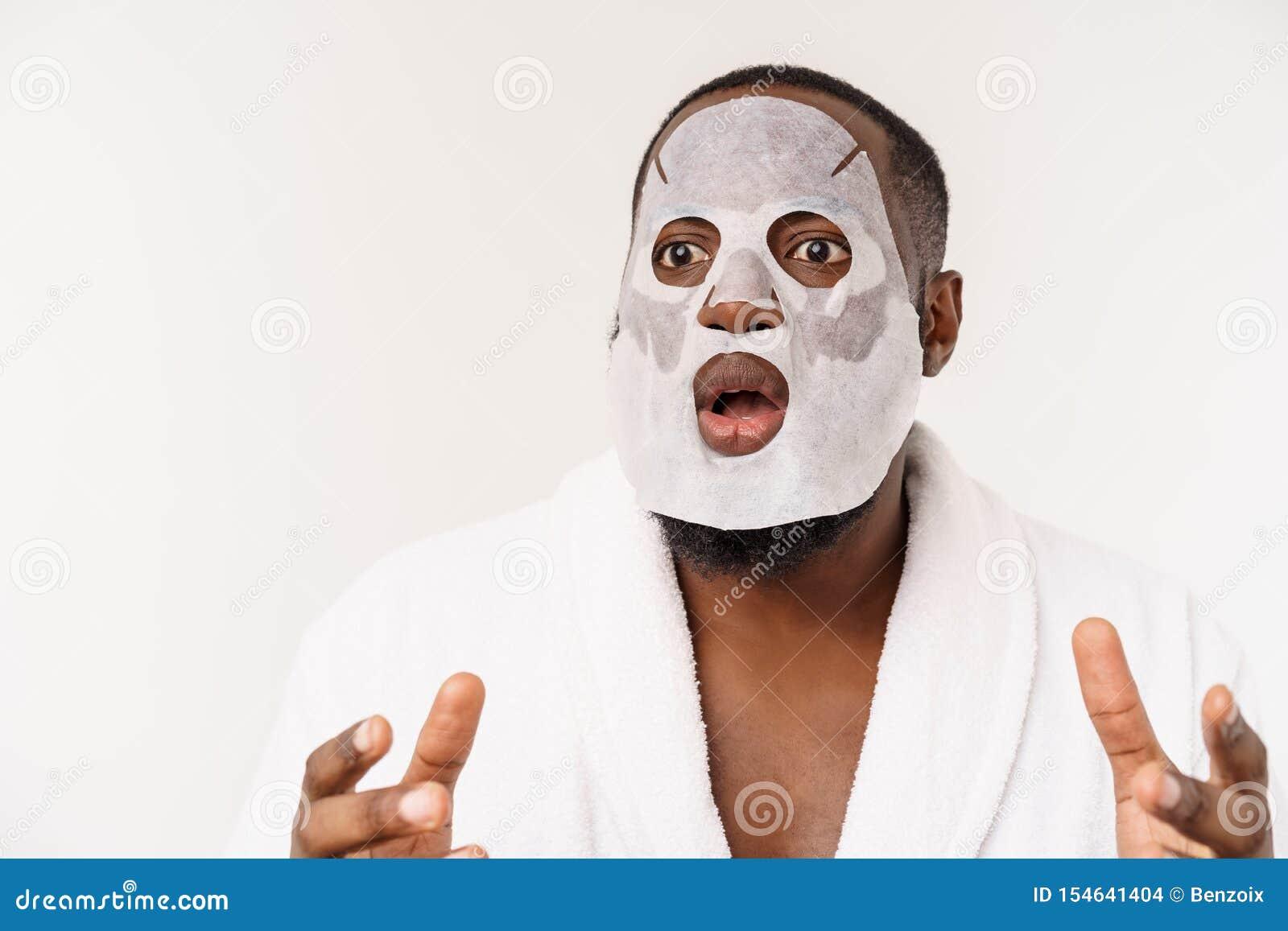 Ein junger Mann mit Papiermaske auf dem Gesicht, das mit einem offenen Mund, lokalisiert auf einem weißen Hintergrund entsetzt sc