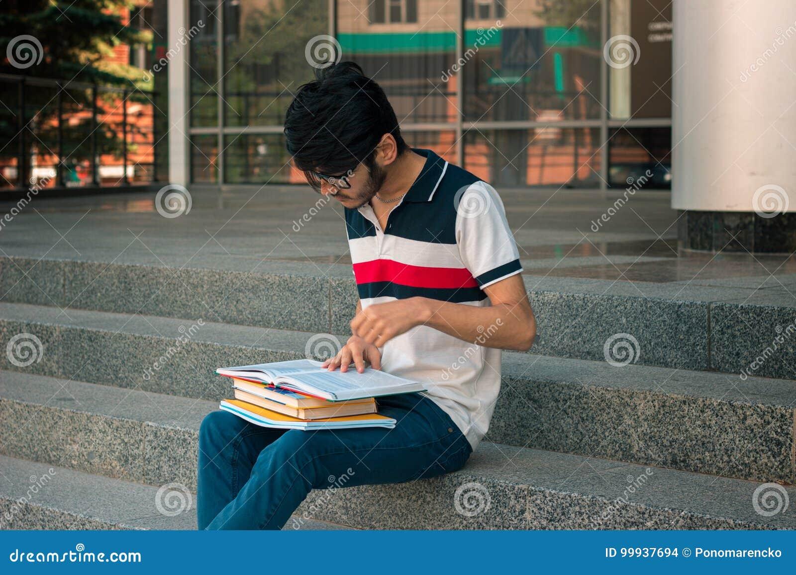 Ein junger Student in einem T-Shirt und Gläser, die auf Gesicht lesen, buchen