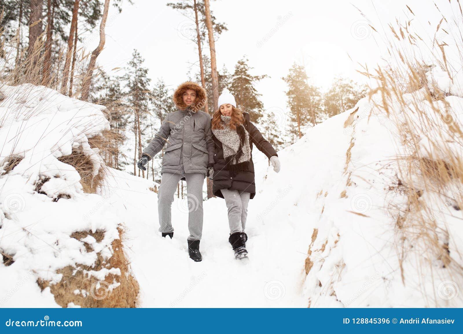 Ein junges Paar, ein Mann und eine Frau gehen in einen schneebedeckten Wald des Winters
