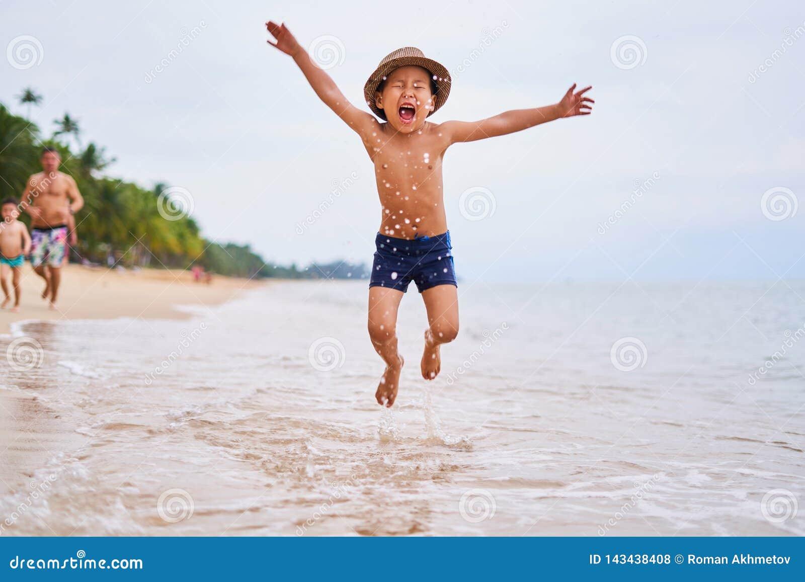 Ein Kind in einem Hut springt auf den Ozean - asiatischer Junge in einem Hut, unscharfer Hintergrund