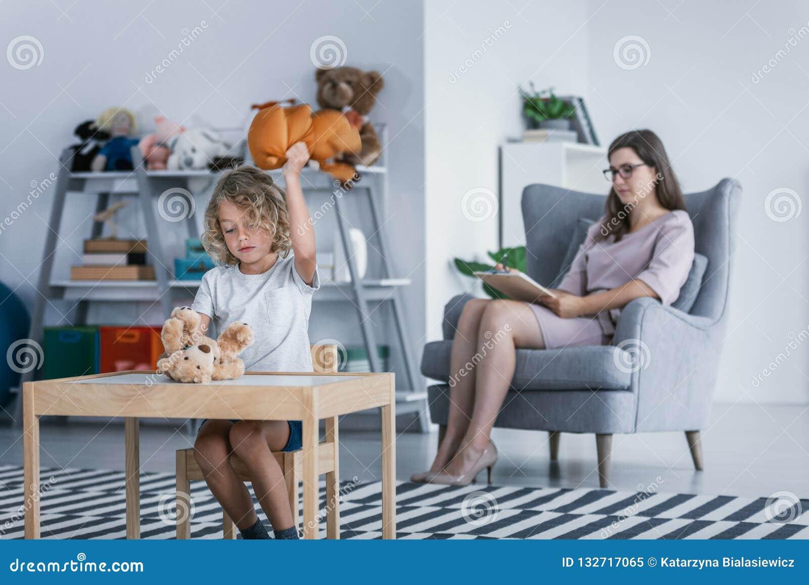 Ein Kind mit den Verhaltensproblemen, die einen Teddybären während einer therapeutischen Sitzung mit einem Therapeuten in a schla
