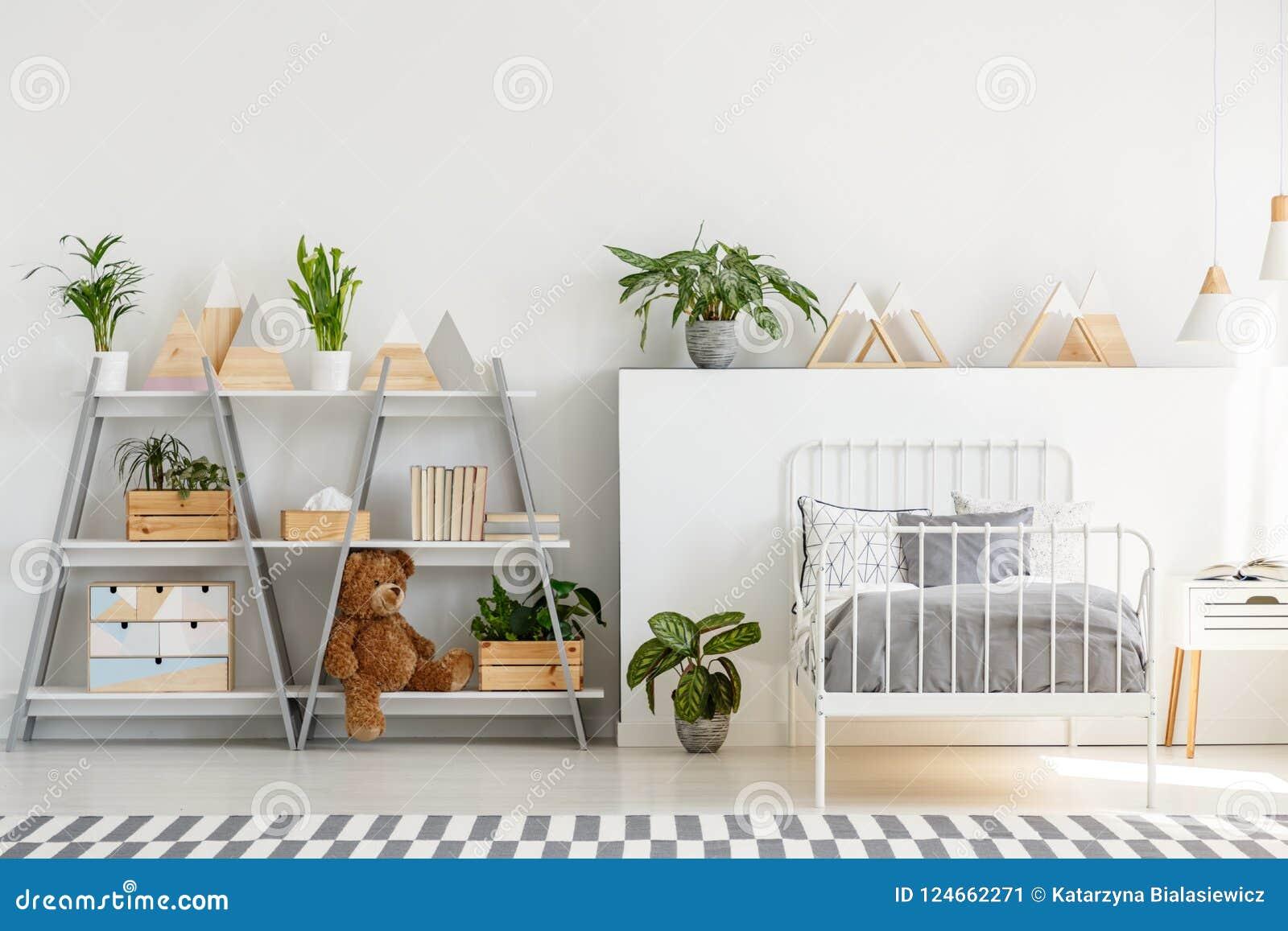 Ein klassischer Kinderschlafzimmerinnenraum mit den einfachen, skandinavischen Artmöbeln und einem grauen hölzernen Bücherschrank