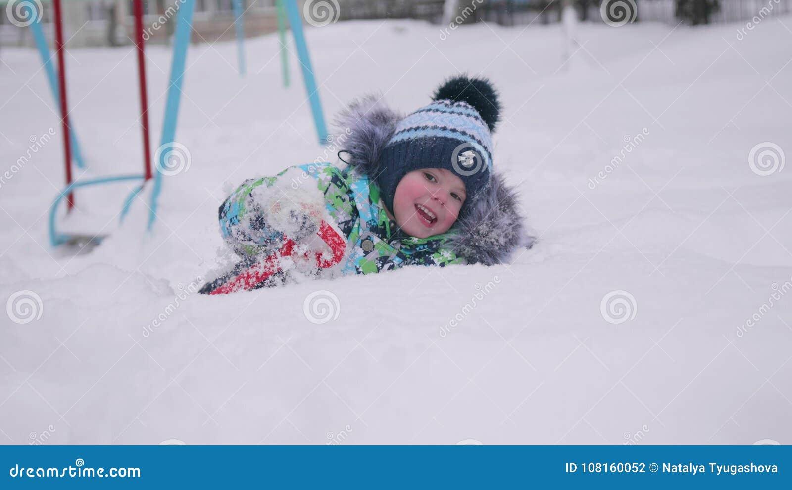 Ein kleines Kind, das mit Schnee in Winter Park spielt Lügenund lächelndes Baby auf weißem flaumigem Schnee Spaß und Spiele im fr