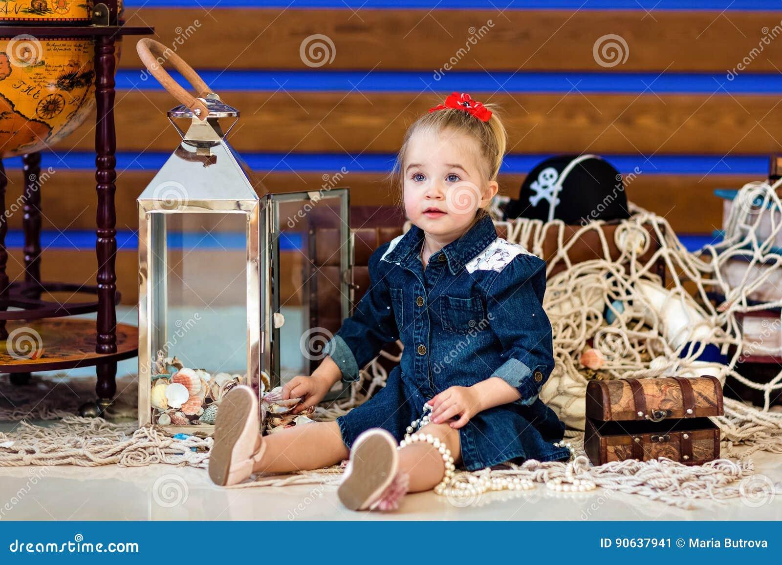 Ein kleines Kind in einem Jeanskleid, das nahe bei einer Kugel sitzt