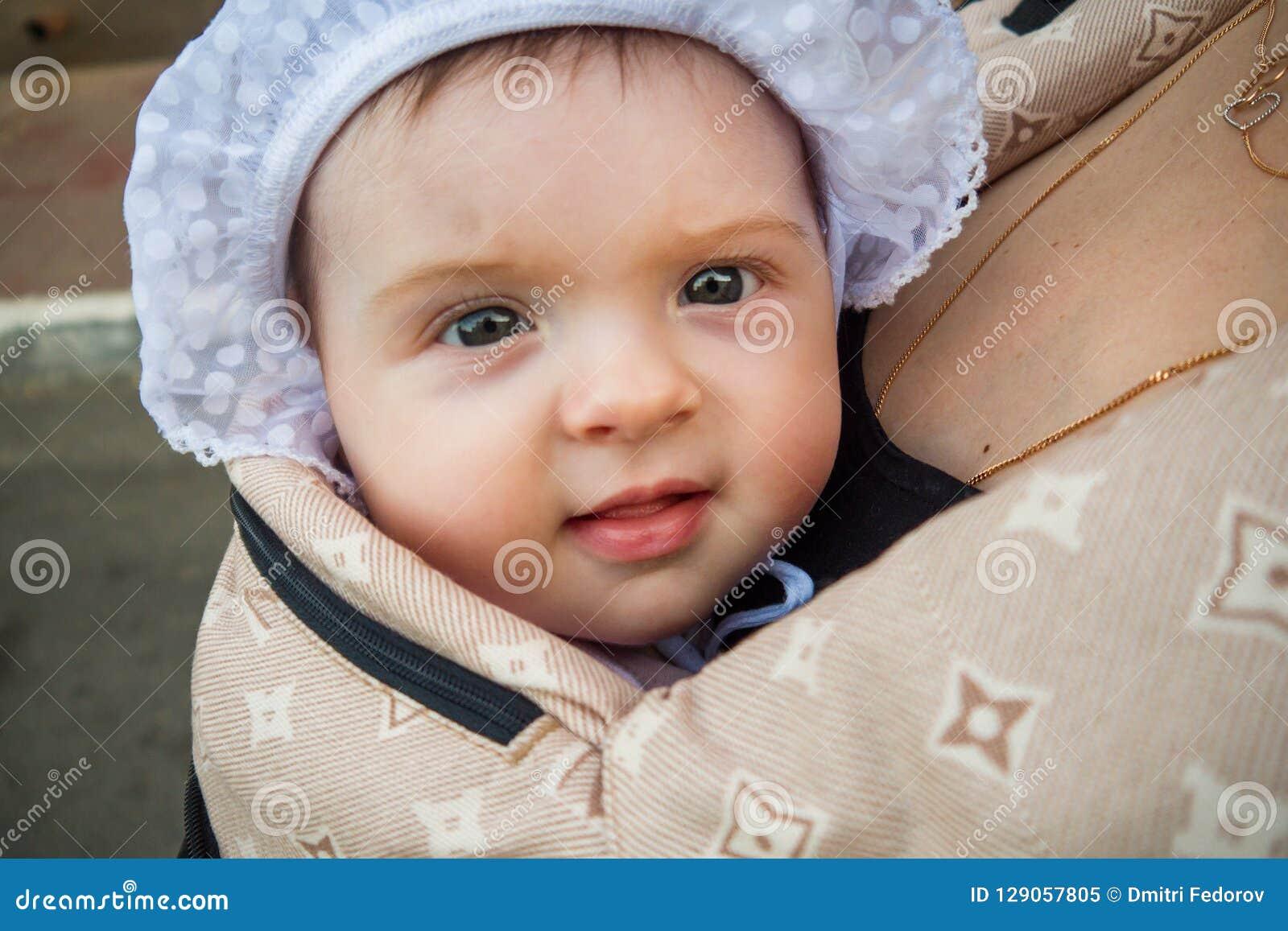 Ein kleines Kind in einem Kind-` s Rucksack mit Mutter Hälfte ein jähriges Baby Weg hinunter die Straße