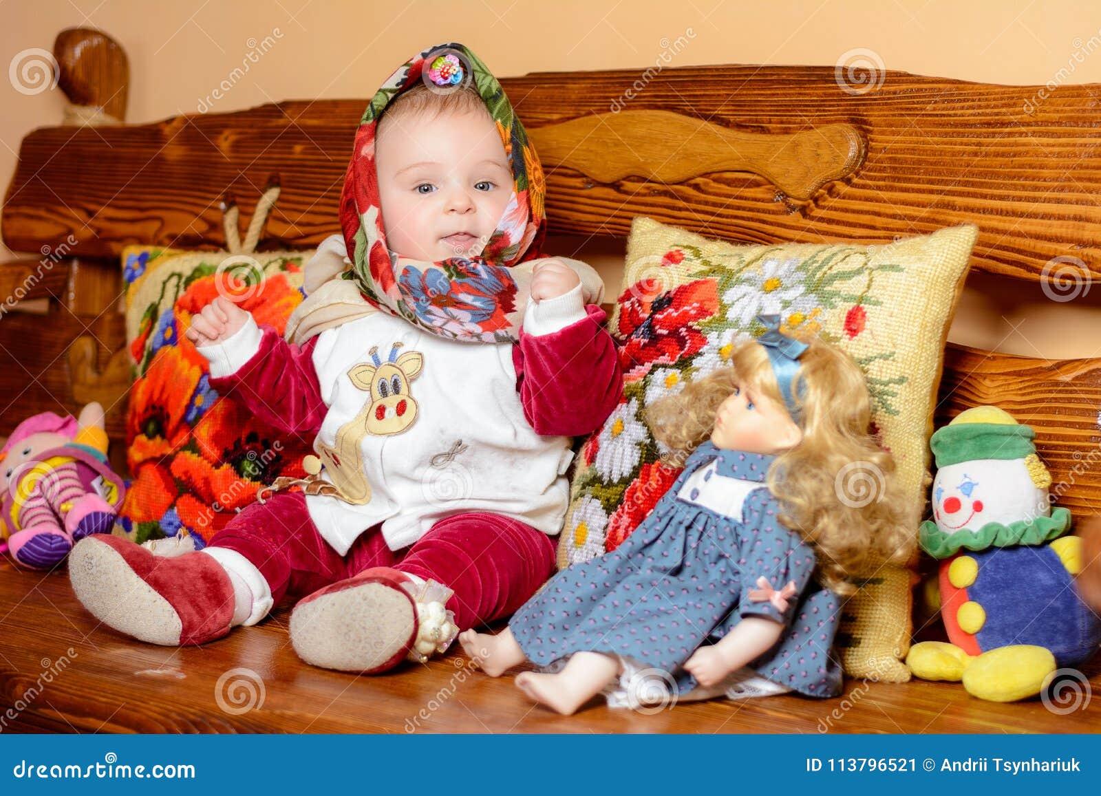 Ein kleines Kind in einem Schal, der auf einem Sofa mit gestickten Kissen sitzt