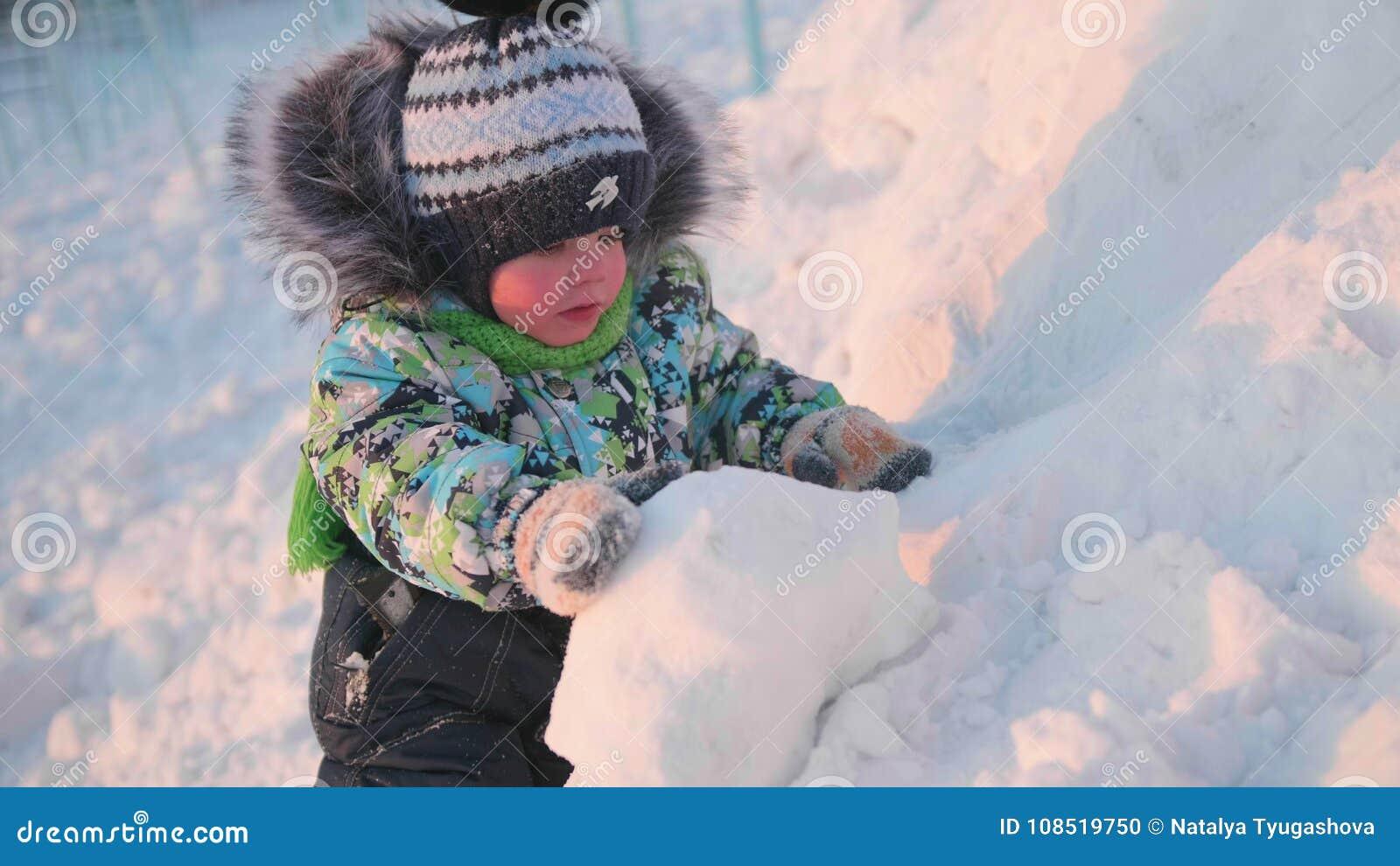 Ein kleines Kind spielt in einem Winter Park mit Schnee Ein sonniger Wintertag Spaß und Spiele in der Frischluft
