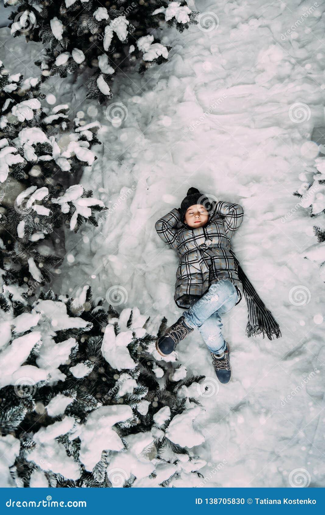 Ein kleines Mädchen in der Winterkleidung, die auf einer schneebedeckten Wieseneinfassung liegt