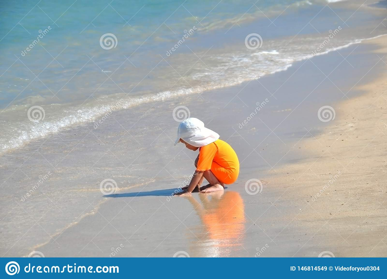 Ein kleines Mädchen in einem orange Badeanzug sitzt auf dem Strand an einem sonnigen Tag