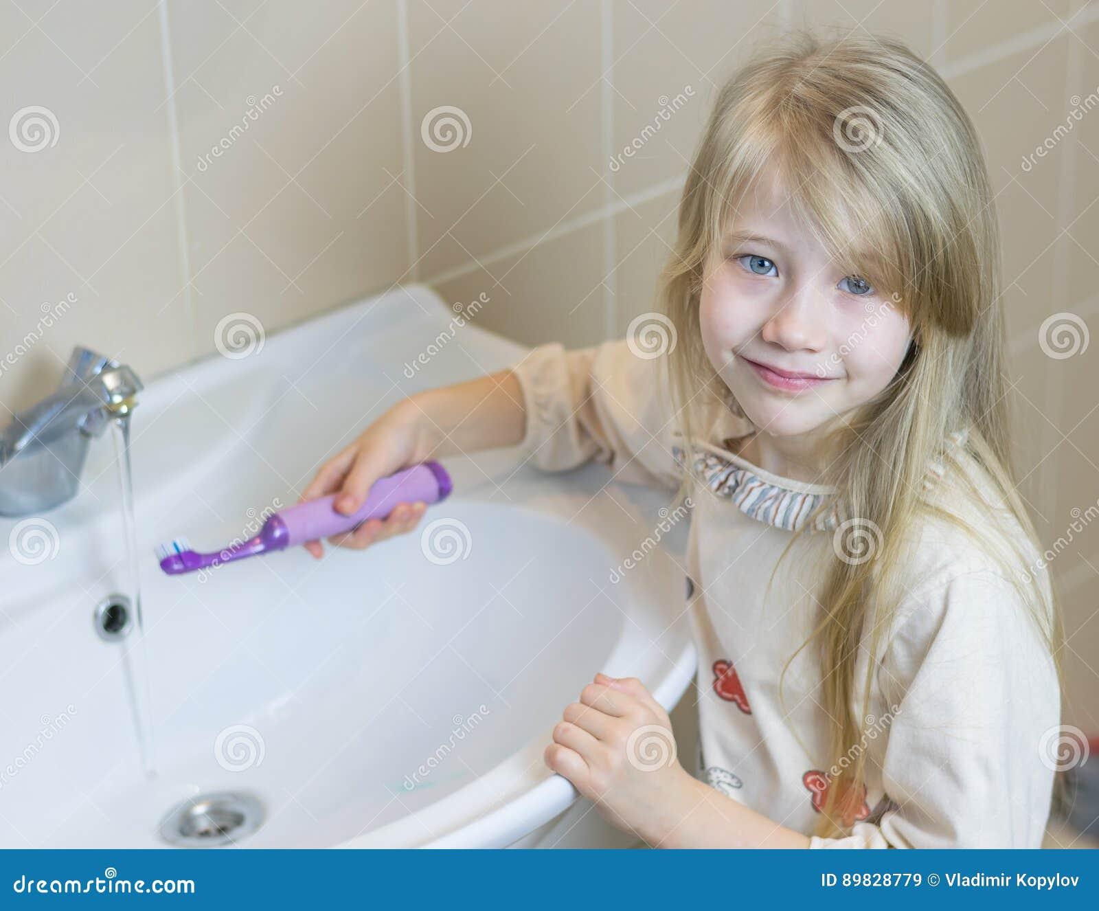 Ein Kleines Mädchen Im Badezimmer Wäscht Eine Elektrische Zahnbürste ...