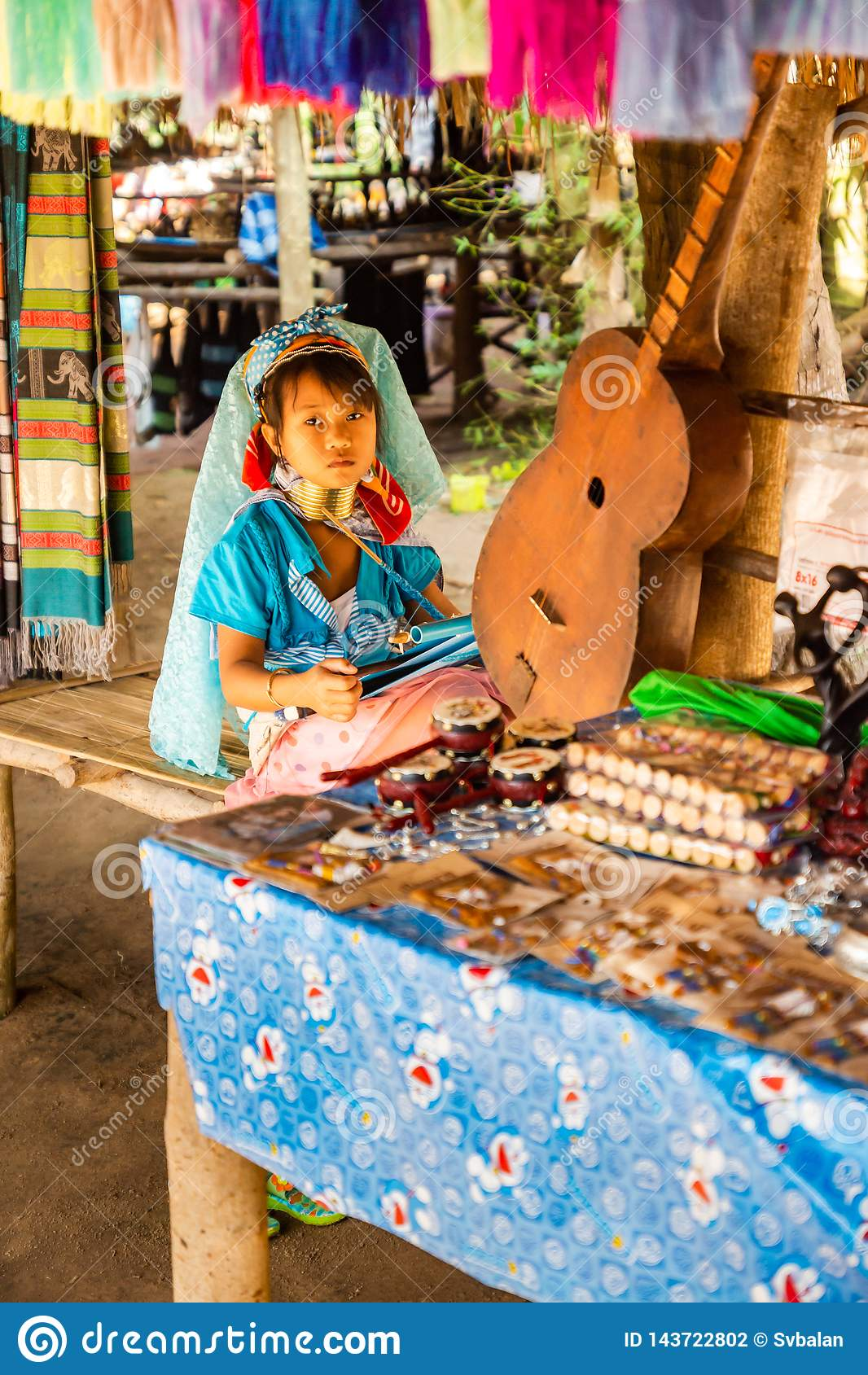 Ein kleines Mädchen mit einem langen Hals und Ringe auf ihrer Herstellungsseide im langen Halsdorf