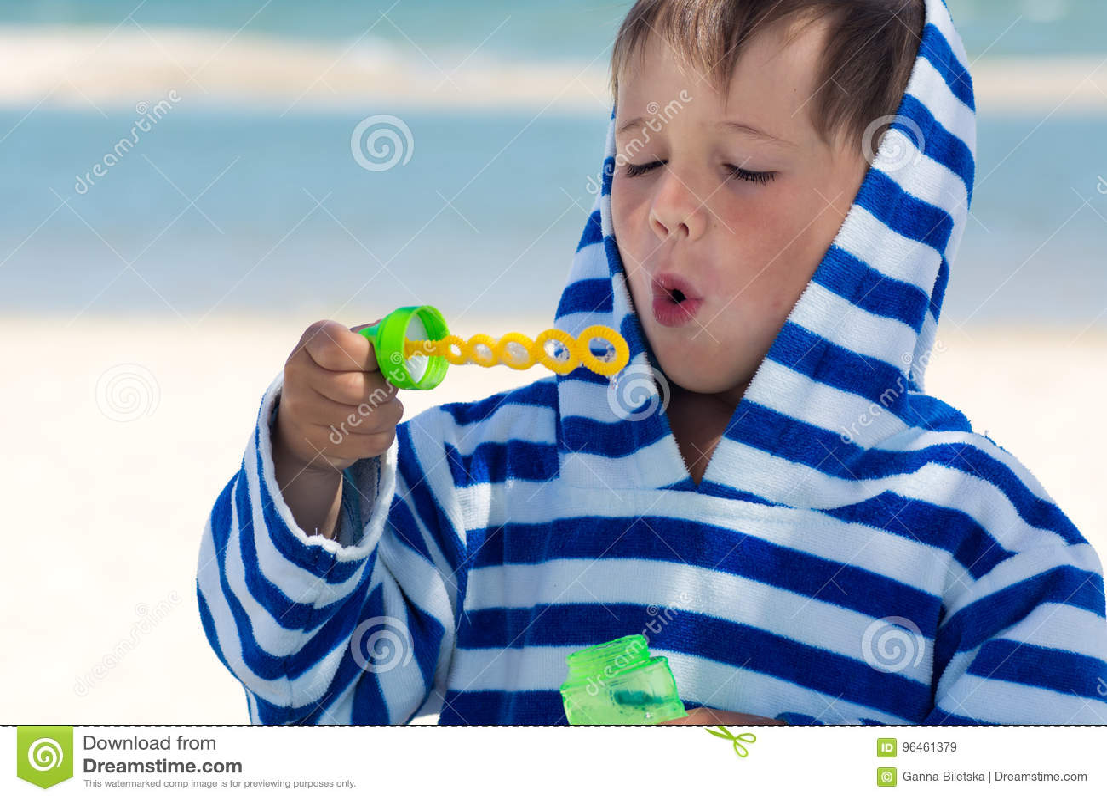Ein kleines nettes Kind in einer gestreiften Robe brennt Seifenblasen vor dem hintergrund des Meeres und der gewaschenen Borte du