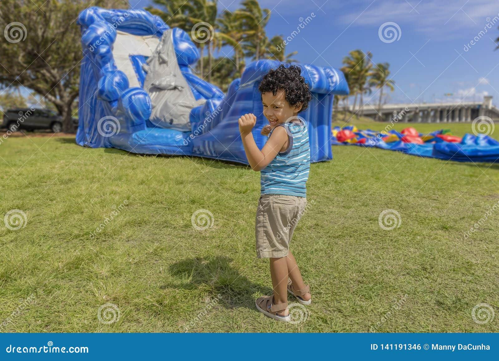 Ein Kleinkind tut seinen glücklichen Tanz beim Aufpassen eines Schlaghauses aufzublasen