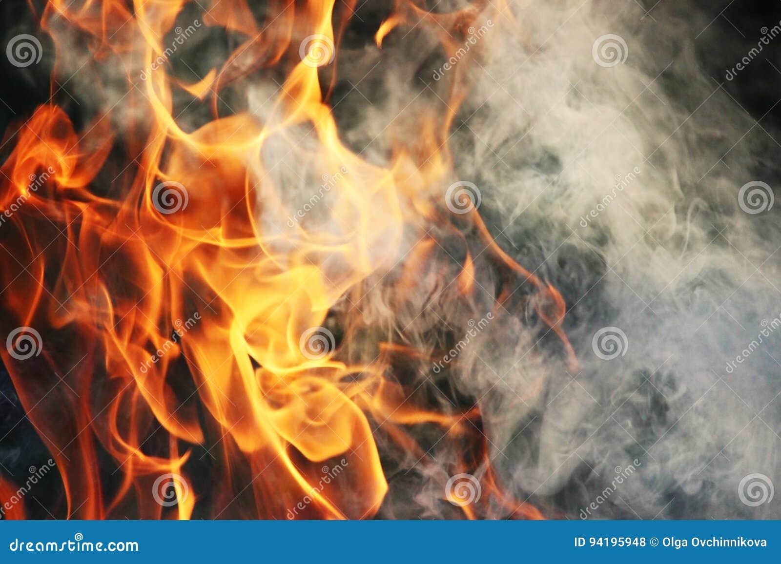 Ein Kulttanz des Feuers und des Rauches gegen einen Hintergrund des grünen Grases Drei Elemente