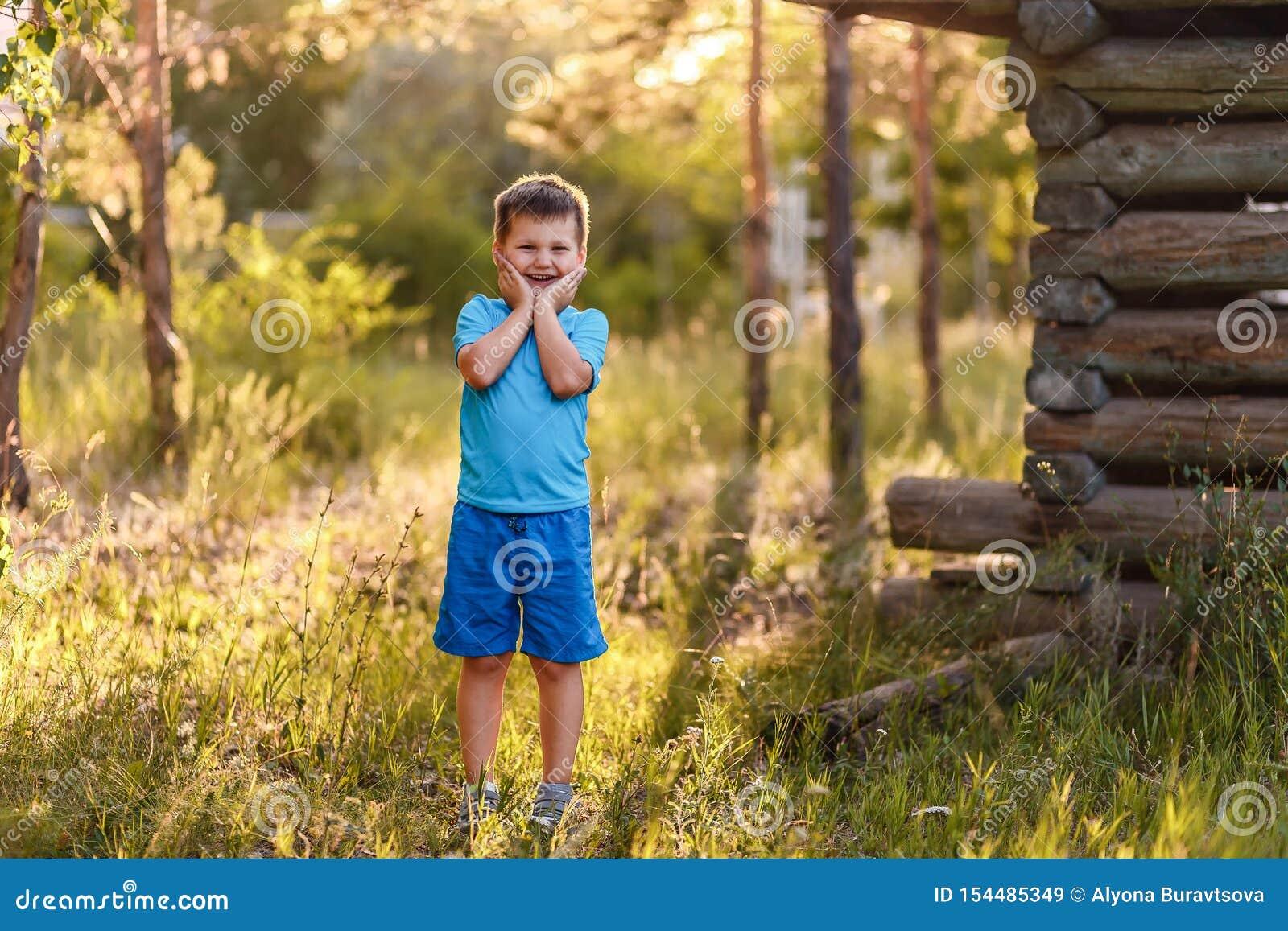 Ein lächelnder fünfjähriger Junge in der blauen Kleidung steht im Park auf einem natürlichen Hintergrund im Sommer im Kontra Sonn