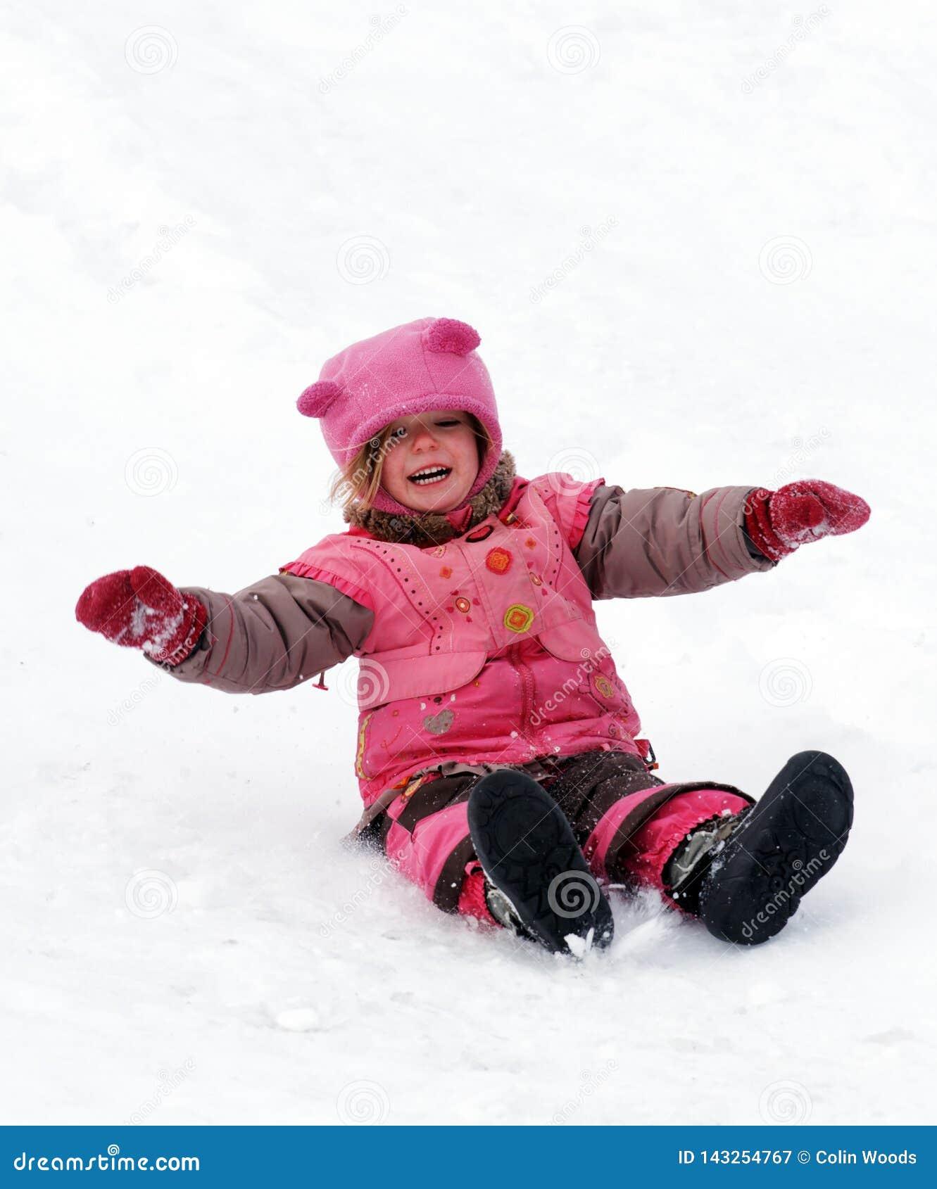 Ein lachendes Kind, das in den Schnee schiebt