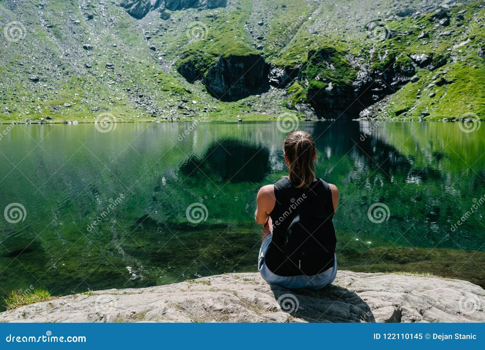 Ein Mädchen, das auf einem Felsen, eine großartige Ansicht des Berges betrachtend sitzt, der im See sich reflektiert