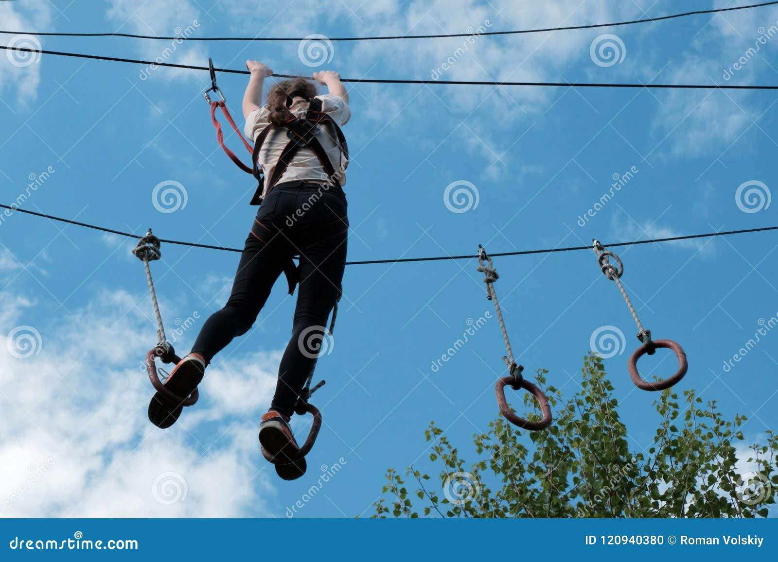 Ein Mädchen, das im Treetoperlebnispark ziplining ist Kletternder Hochseilpark Durchgang des Hindernislaufs über Bäumen gegen den