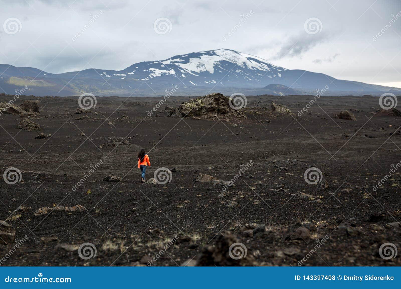 Ein Mädchen in einer orange Jacke geht durch ein ausgebranntes Lavafeld