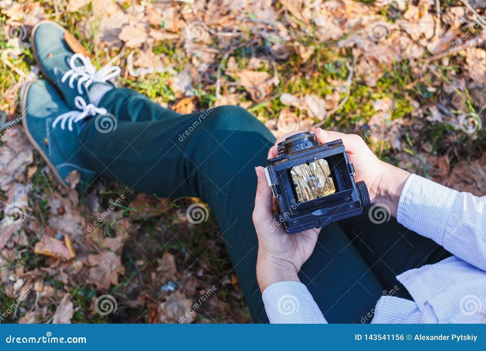 Ein Mädchen hält in ihren Händen einen alten Wald der Filmfoto-Kamera im Frühjahr