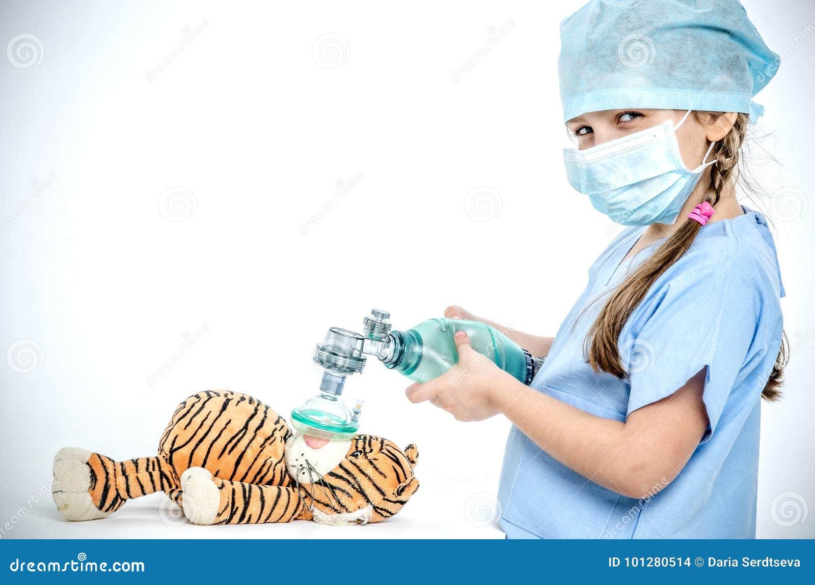 Ein Mädchen kleidete Griffen einer in den chirurgischen Klage einen Botschafter über einem Spielzeugtiger und macht Belüftung der