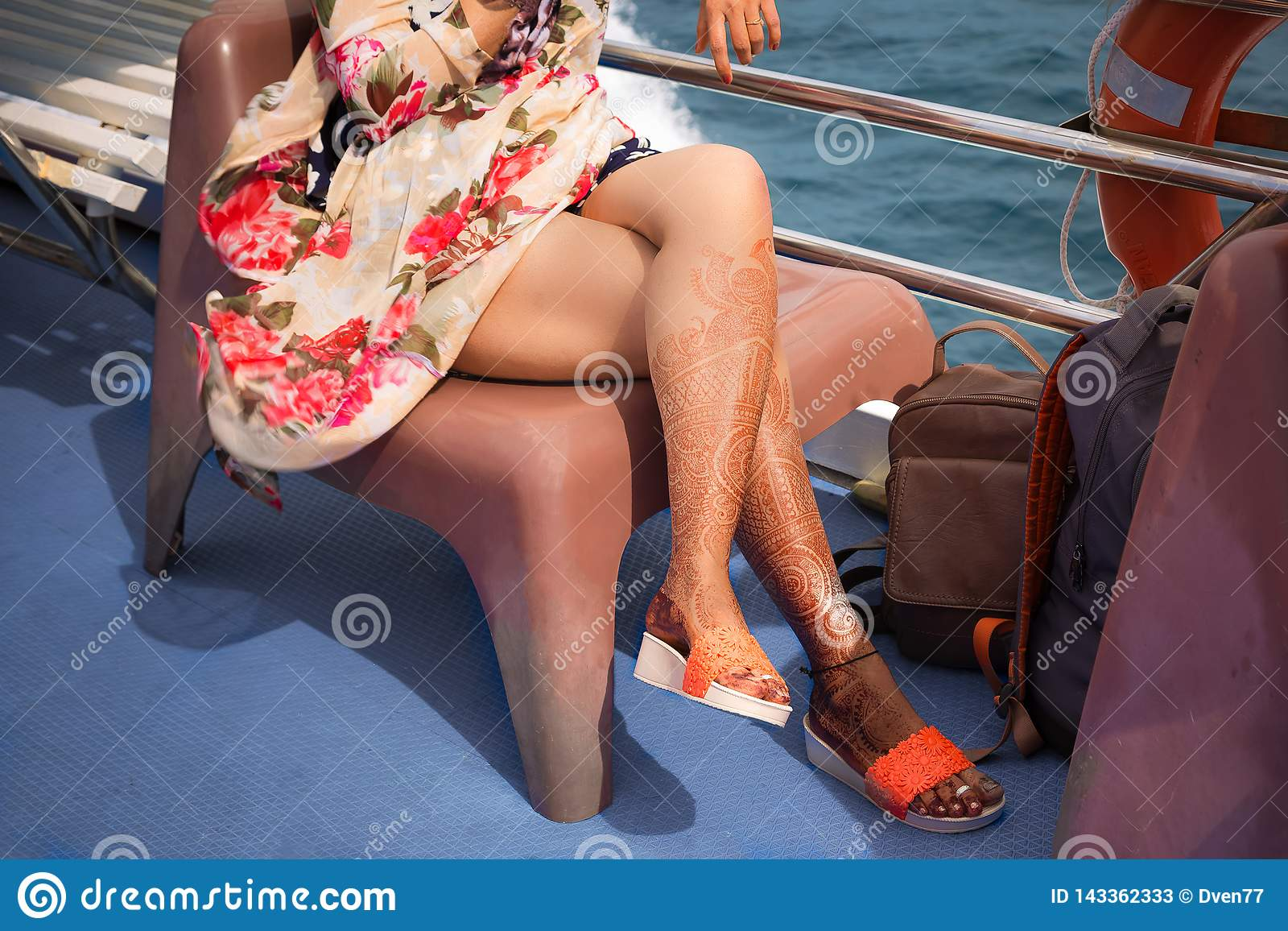 Ein Mädchen mit vorübergehenden Hennastrauchtätowierungen auf ihren Beinen Sitzt im bunten Kleid auf einem Stuhl auf einem Kreuzs