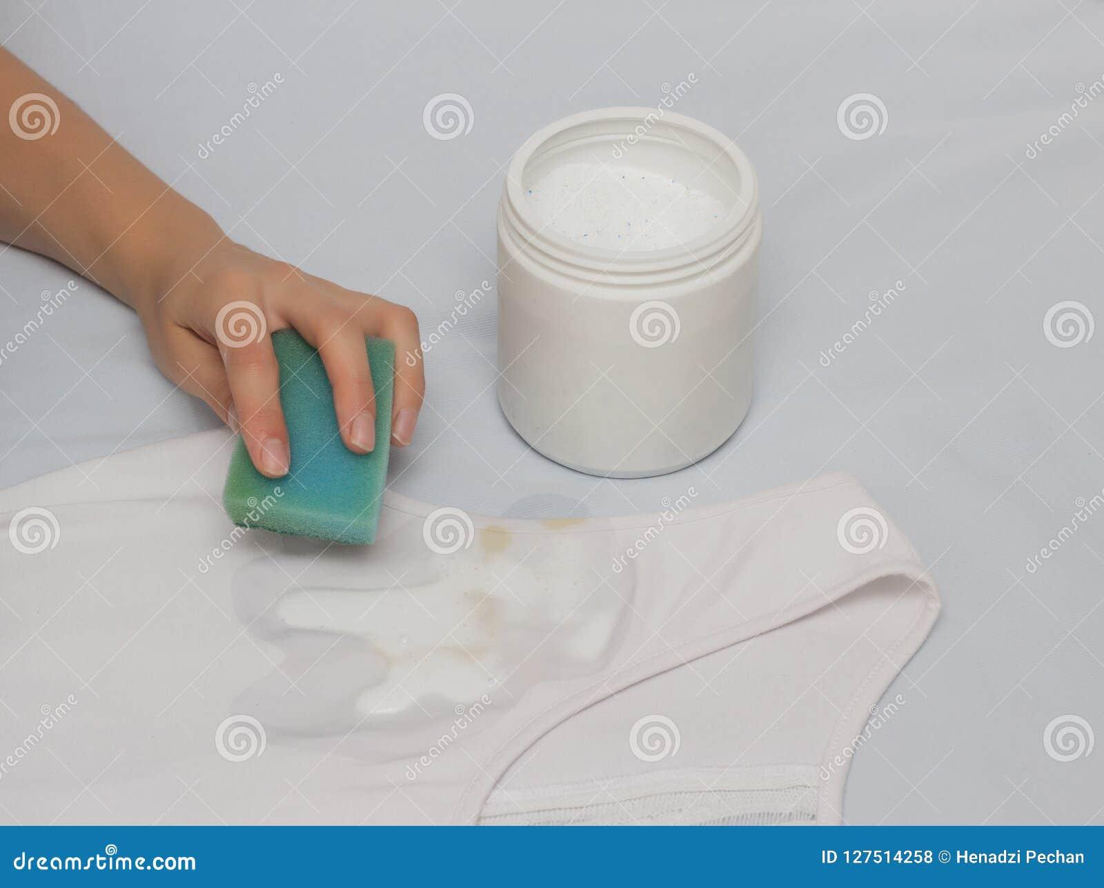 Ein Mädchen säubert einen Fleck mit einem Schwamm auf einem T-Shirt unter Verwendung eines Fleckenentferners, Nahaufnahme, Hand
