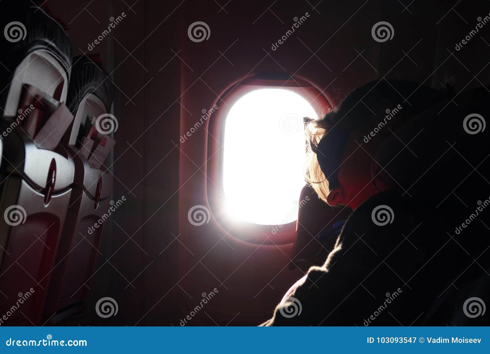 Ein Mädchen schläft in einem Flugzeugstuhl in einer Maske vor der Öffnung während des Fluges Schattenbild gegen einen hellen Sonn