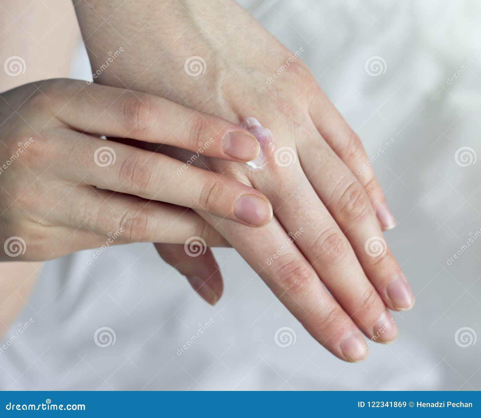 Ein Mädchen schmiert eine Handcreme auf einer weißen Hintergrundcreme