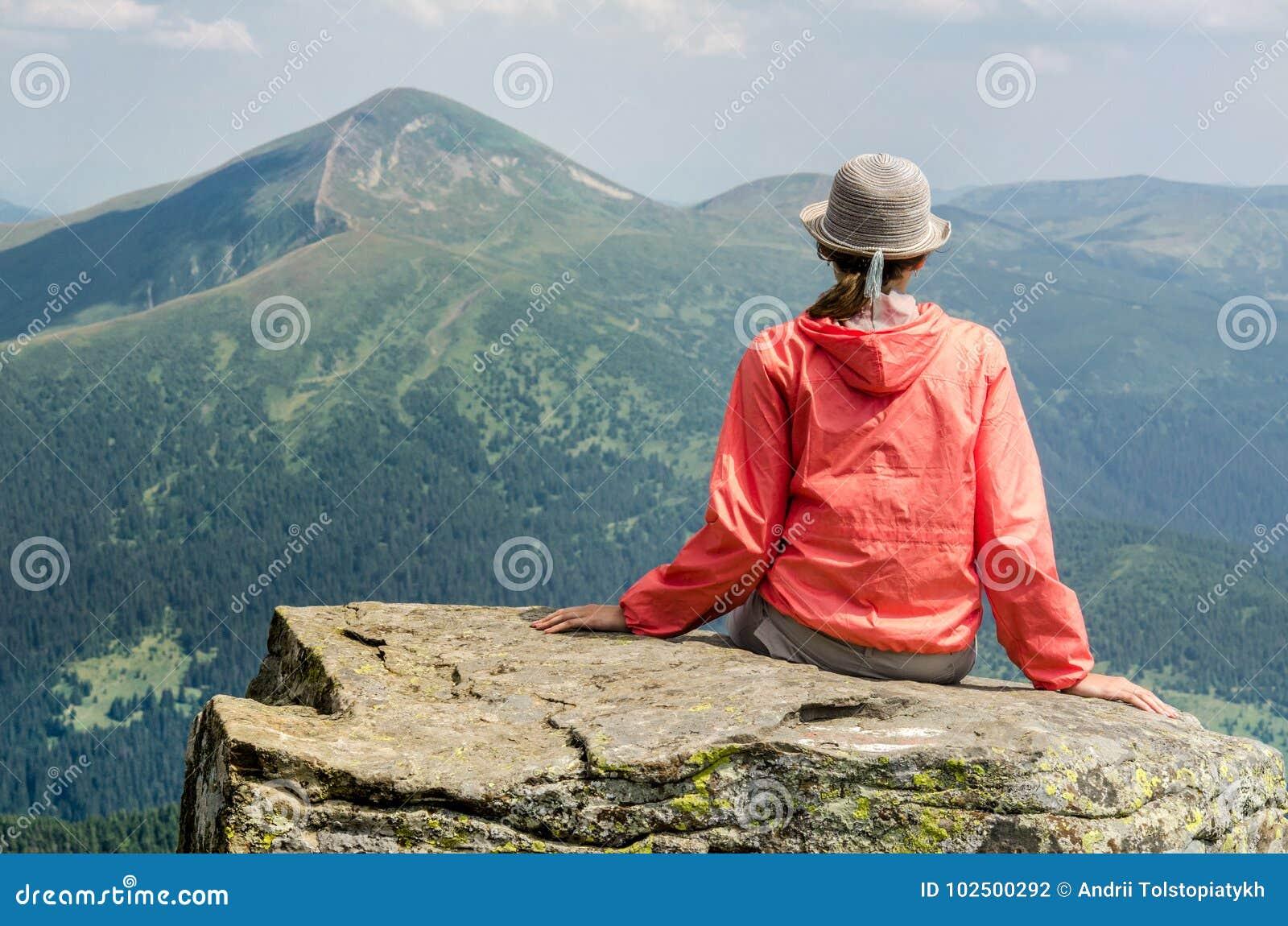 Ein Mädchen sitzt auf einem Stein und meditiert