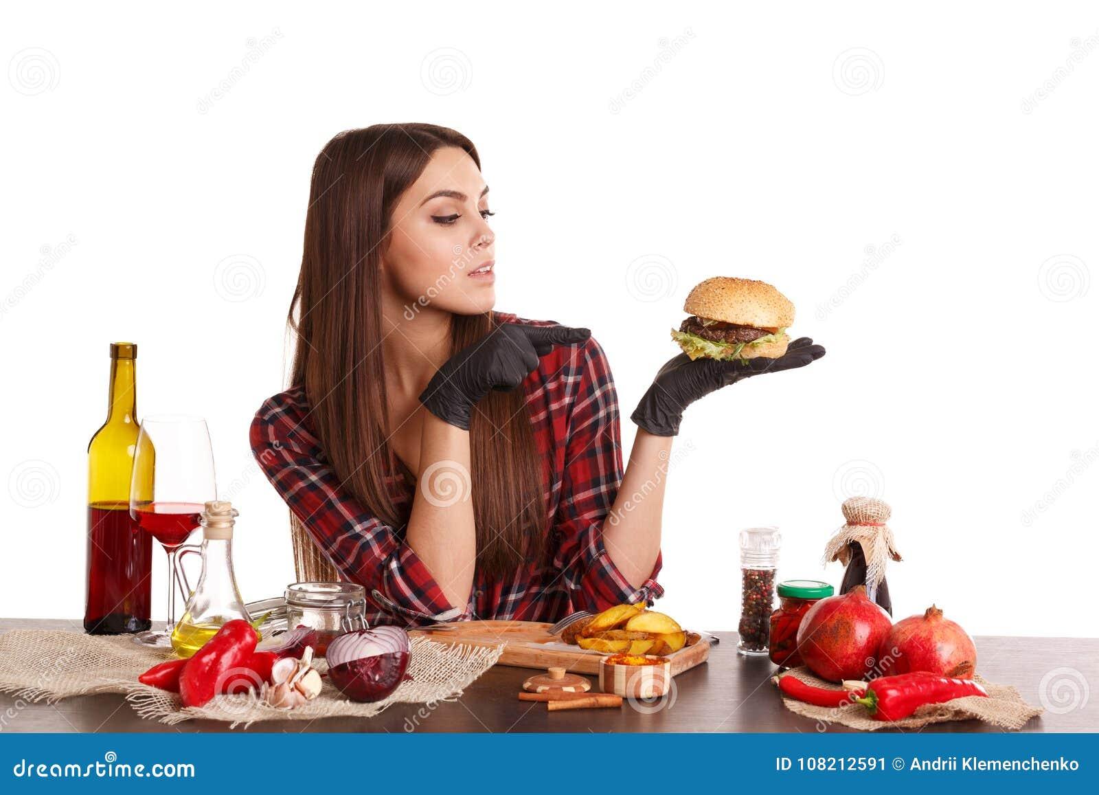 Ein Mädchen, sitzt an einem Tisch mit Lebensmittel, hält einen Burger und Punkte an ihm mit dem Finger Getrennt auf weißem Hinter