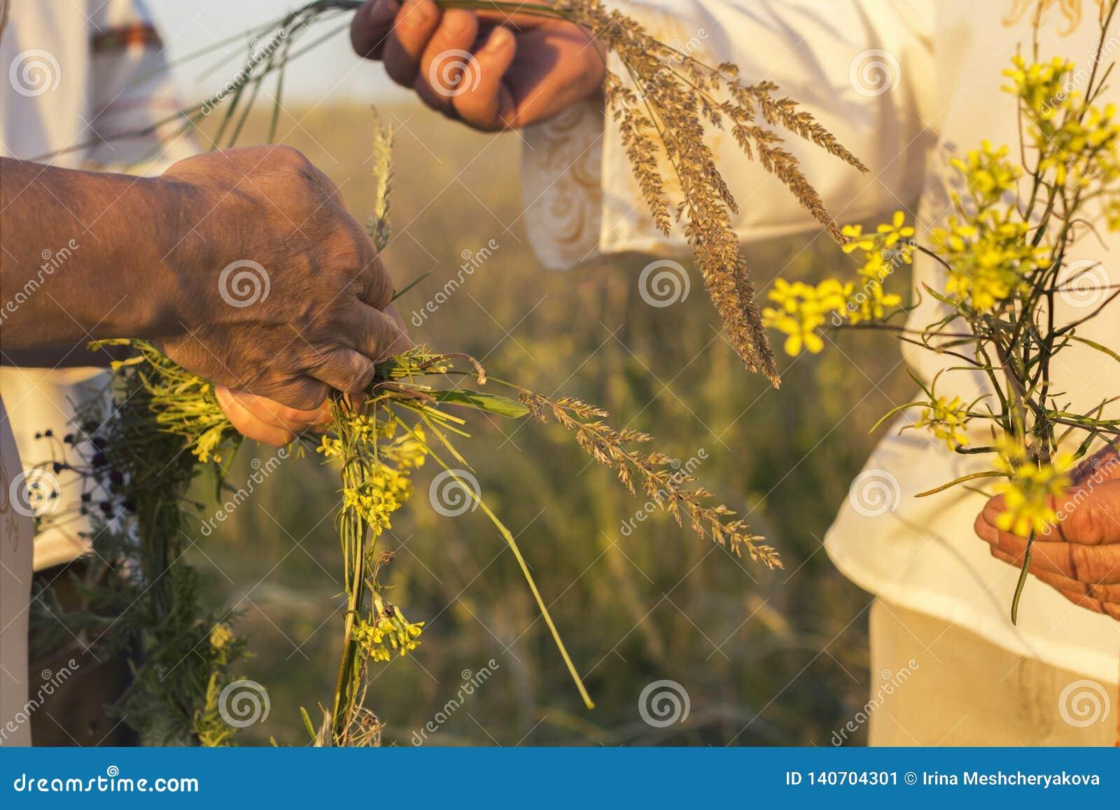 Ein Mädchen und ein Mann im weißen traditionellen slawischen Kleid windt einen Kranz von frischen Wildflowers bei Sonnenuntergang