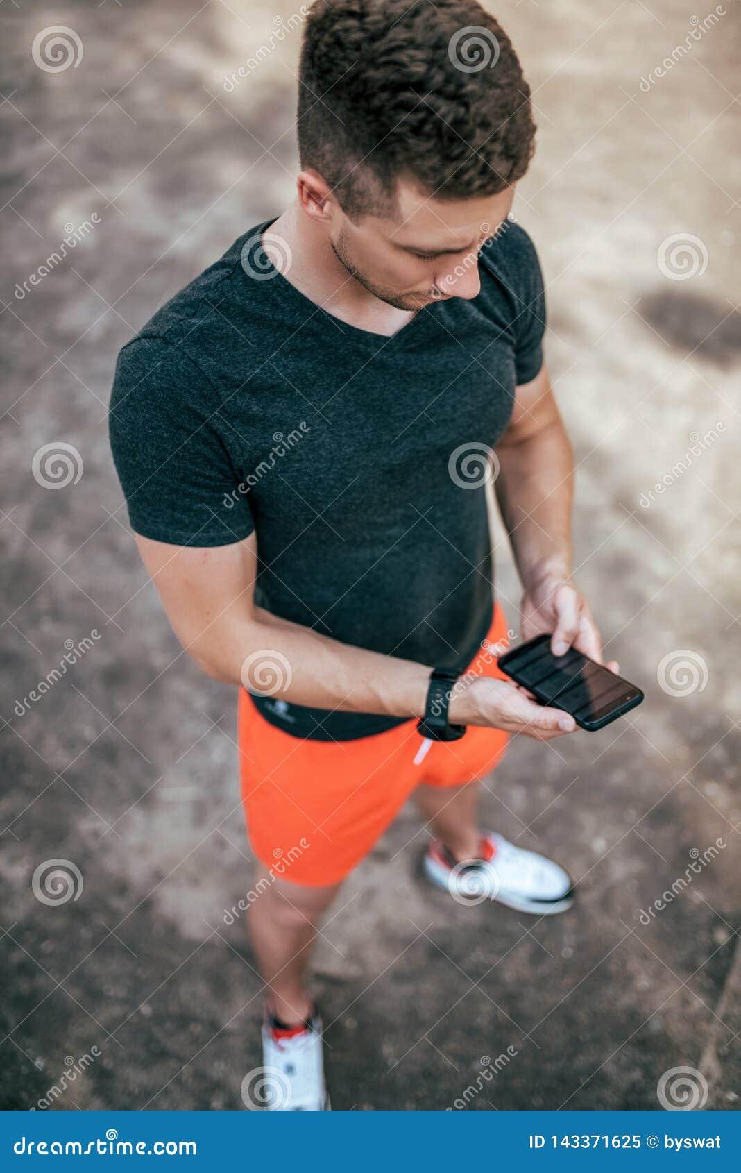 Ein männlicher Athlet, Sommerstadt auf Sportfeld, hält Telefon in seiner Hand, eine Wahl von Internet-Anwendungen, on-line-Traini