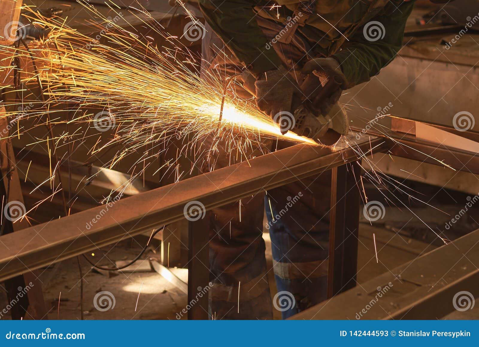 Ein Mann in Arbeitsformschnitten, die ein Metall mit einem Bulgaren sah