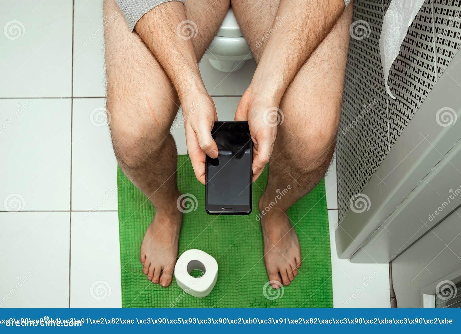Ein Mann, der auf der Toilette hält einen Smartphone in seinen Händen, Draufsicht sitzt Das Konzept von Problemen mit dem Stuhl